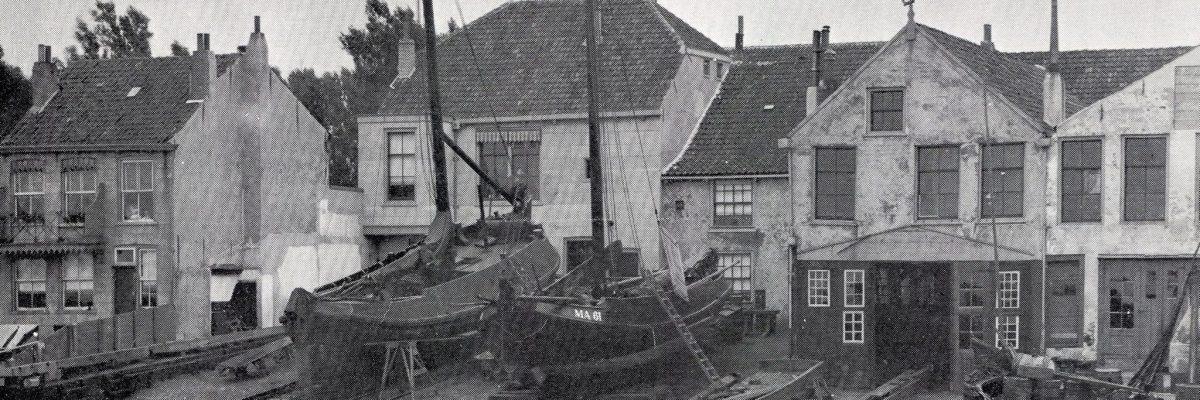 """Oude scheepswerf aan de Noordgeer aan de achterzijde van de Olivierstraat met daarop onder andere motorbotter MA61, voor de wal enkele Westlanders en een Bom. De MA61, die op de helling ligt, is van ongeveer 1910 tot 1918 voor een Maassluise reder in de vaart geweest. Periode 1879-1979: Scheepmaker Hendrik de Haas, de grondlegger van de huidige scheepswerf De Haas, werd in 1869 door Willem Firet, eigenaar van een kleine scheepswerf aan de Noordvliet, van Wateringen naar Maassluis gehaald. Zijn droom om ooit de werf over te nemen ging na negen jaar werken in rook op door het overlijden van Firet. Sinds 1875 was er sprake van een aanzienlijke opleving in de handel, industrie en scheepvaart. Ook  de haringvisserij was weer opgebloeid, mede door de introductie van de logger. Reden voor Hendrik de Haas de grote stap te wagen: in 1879 huurde hij van Jan Maurisse een aan de Olivierstraat gelegen houtloods met erf  en richtte de Scheepmakerij H. de Haas """"Zorg en Vlijt"""" op.  Zijn zoons Piet, Hein en Jan traden bij hem in dienst; zoon Gijs bleef varen. Door het aanleggen van een houten vetgoothelling, die via openslaande deuren tot half in de loods doorliep, kon men overdekt werken.  Kennelijk ging het hen voor de wind, want al snel huurde De Haas een naast liggend stuk grond en bouwde een zwaardere en langere vetgoothelling, zodat ook loggers kon worden gehellingd. In 1884 kon Hendrik de Haas van de erfgenamen van Jan Maurisse de gehuurde percelen en een aangrenzende kuiperij kopen.  De kuiperij werd gesloopt en De Haas liet een nieuw woonhuis bouwen, waarvan de familie de bovenverdieping betrok. Beneden werd een stoominrichting geplaatst, die zowel de nieuwe, derde vetgoothelling als de andere twee hellingen kon bedienen. Helaas kon Hendrik de Haas slechts vier jaar van zijn nieuwe huis genieten. Op 7 juli 1899 kwam hij te overlijden en namen zijn zoons de leiding over. *** Local Caption *** zie boekwerkje """"Zij hielden de vaart erin"""" - uitgegeven ter gelegenheid van het 100"""
