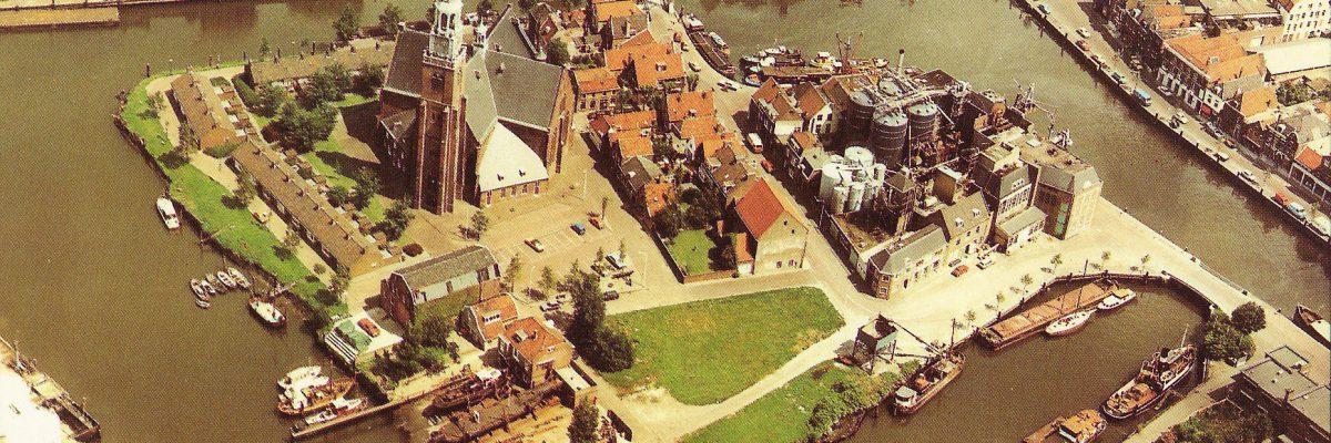 Luchtfoto van het Schanseiland gezien vanuit het westen met centraal de Groote Kerk. Rechts op het eiland de oliefabriek De Ploeg. Onder de bedrijfsterreinen van scheepswerf De Haas aan het Hellinggat. Verder rechts de Binnenhaven met de Havenkom en de Stadhuiskade en links de Noordgeer.